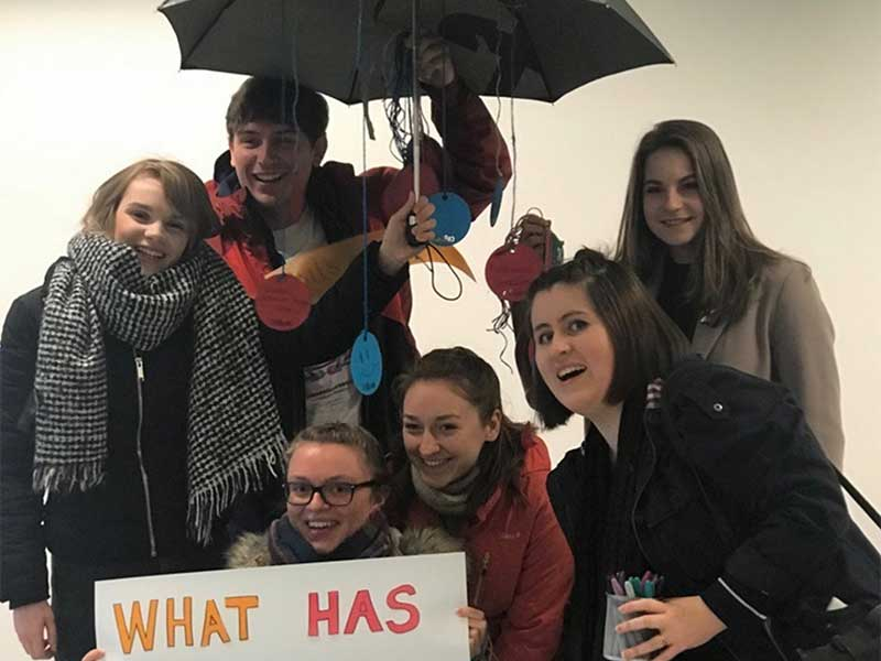 Young people standing underneath an umbrella