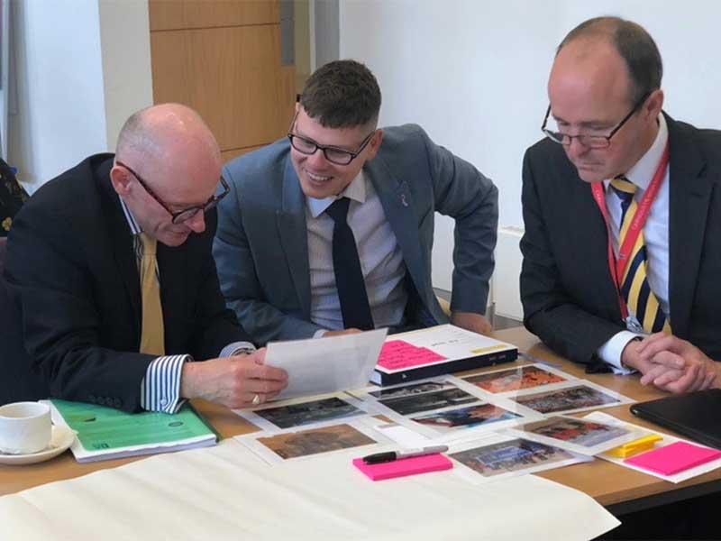 Three men looking at photographs